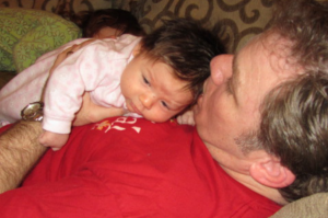 Baby enjoys Tummy Time on dad's stomach.
